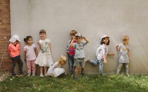 stastne deti pozerajuce do objektivu pred bilingvalnou skolkou v bratislave
