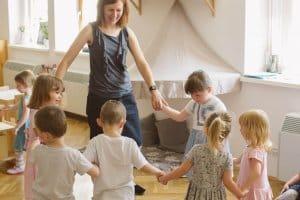stastne deti sa hraju so sprievodkynkou v montessori hernicke